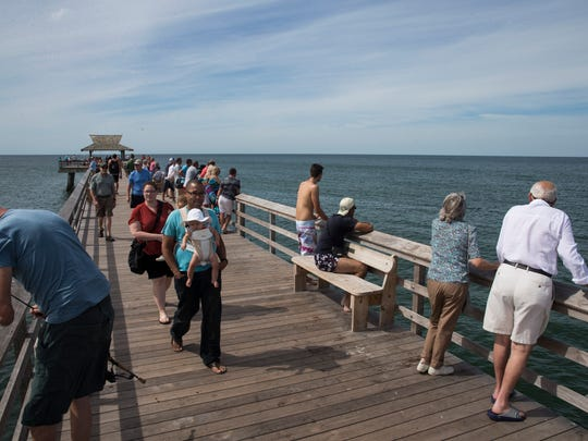 People walk and fish along the pier in downtown Naples, Florida on Tuesday, Oct. 25, 2016.