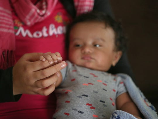 Maira Aguilera holds one of her 4-month-old twins,