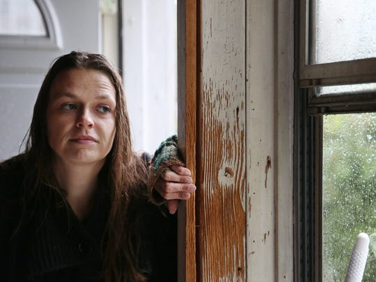 Kara Helstrom looks out at the rain from her back porch at her home on Jackson Street in Geneva Friday, Oct. 21, 2016.