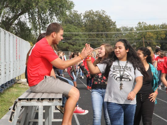 CIS health teacher Matt Enloe gives students a high five as they pass by during the walkathon.