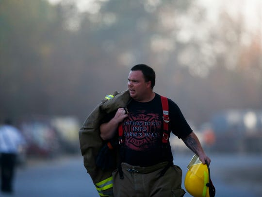 An Alabaster firefighter walks near the scene of an explosion of a Colonial Pipeline, Monday, Oct. 31, 2016, in Helena, Ala. Colonial Pipeline said in a statement that it has shut down its main pipeline in Alabama after the explosion in a rural part of the state outside Birmingham.
