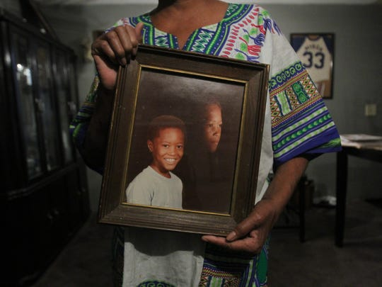 Sandra Traylor holds a portrait of her nephew, Myron Traylor, 13, who disappeared in south Phoenix in 1988.