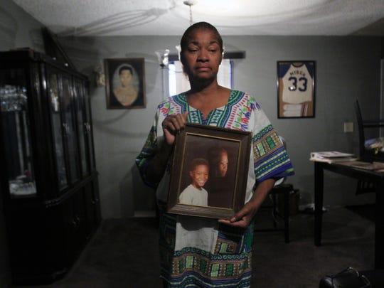 Sandra Traylor holds a portrait of her nephew, Myron Traylor, 13, who vanished in 1988 on the way to his grandmother's home in south Phoenix.
