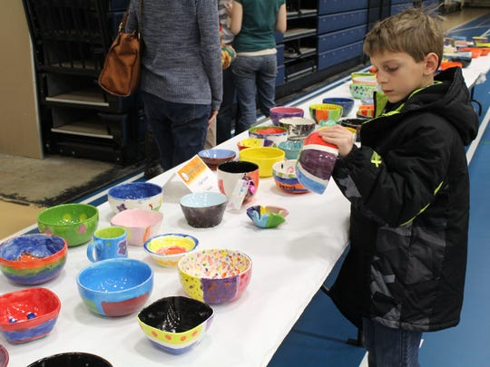 A young boy inspects a bowl at the 2015 Empty Bowls event at Wausau West High School.