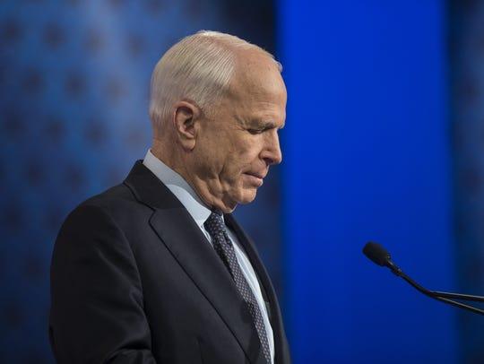 Sen. John McCain reads over notes before a debate for
