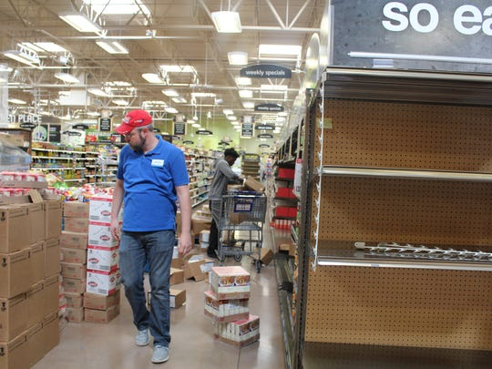 Kroger employees stock the store's shelves before it opens Nov. 18.