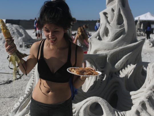 Jeneane Desilets,20, an art student from Chicago, enjoyed the food as she viewed the sand sculptures Sunday at Day two of the American Sand Scuplting Championships at Fort Myers Beach.