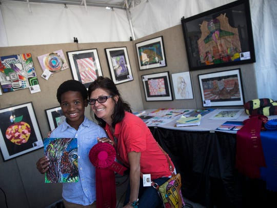 Nalin Isme, 8, stands with HotWorks Executive Director Patty Narozny after winning an award of distinction in the Youth Art Competition during the 18th bi-annual HotWorks.org Estero Fine Art Show at the Miromar Design Center on Sunday, Nov. 20, 2016. As one of the top 100 art fairs in America, the event showcases original and personally handmade art from 175 professional artists.