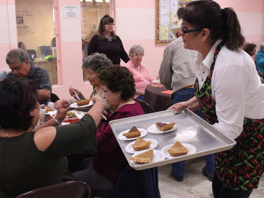 1st New Mexico Bank employee Gloria Renteria becomes the most popular volunteer with the choice of pecan or pumpkin pie during Tuesday's Thanksgiving Dinner for seniors. For the past 20 years, 1st New Mexico Bank and the Deming Senior's Center team up to serve the dinner to an anticipating crowd of hungry seniors.