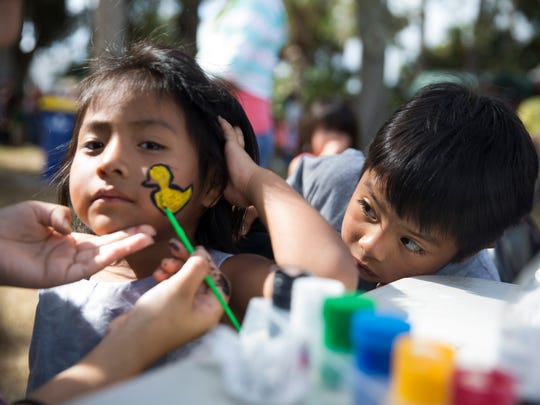 Samuel Perez, 4, gets a sneak peek of the duck being painted on the face of Jennifer Tomas, 2, face at Airport Park in Immokalee on Thursday, Nov. 24, 2016. Hundreds of people from the Immokalee community came out on Thanksgiving Day to receive a meal donated by the Guadalupe Center and St. John the Evangelist Catholic Church.