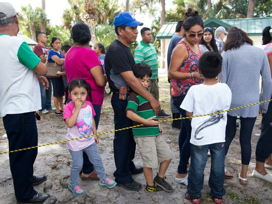 Pedro Mateo, center, and his son Aden Salvado, 6, patiently wait in line for a Thanksgiving meal donated by the Guadalupe Center and St. John the Evangelist Catholic Church at Airport Park Thursday, Nov. 24, 2016 in Immokalee.