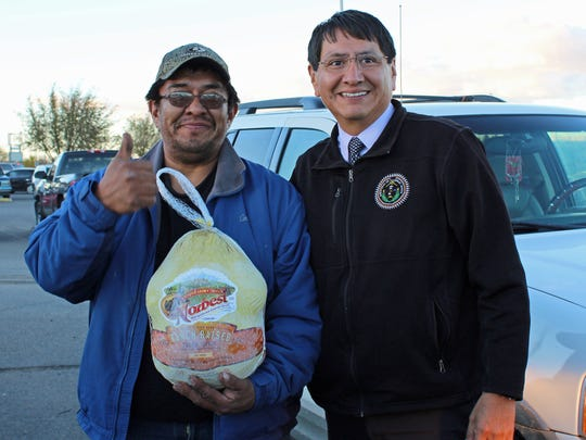 Navajo Nation Vice President Jonathan Nez, left, distributed turkeys to Navajo residents in Shiprock on Tuesday.