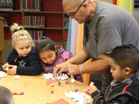 Ervie Ornelas, child care provider at San Jose Child Care Center, helps students make a paper Santa Claus. Ornelas has been a provider for 24 years.