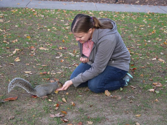 """In this Sept. 28, 2016 photo, Penn State senior Mary Krupa plays with """"Sneezy"""" the squirrel on Old Main Lawn in State College, Pa. Penn State students know her as the Squirrel Whisperer, or even Squirrel Girl. Four years after she became an internet sensation, senior Krupa is still placing tiny hats on the ubiquitous rodents that live on campus, and coaxing them to hold miniature props. (Phoebe Sheehan/Centre Daily Times via AP)"""