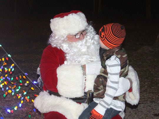 Santa Claus listens to a boy's Christmas wish at the