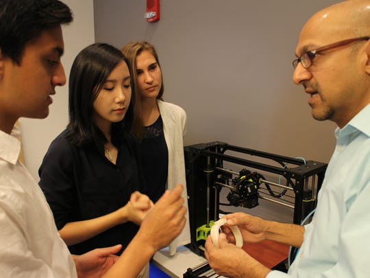 In the Innovation Lab (from left) Yash Sanghavi, Maisy Chung and Patricia Shelton discuss project development with Patel.
