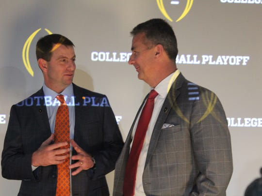 Clemson coach Dabo Swinney and Ohio State coach Urban Meyer talk after the College Football Playoff coaches' press conference in Atlanta.
