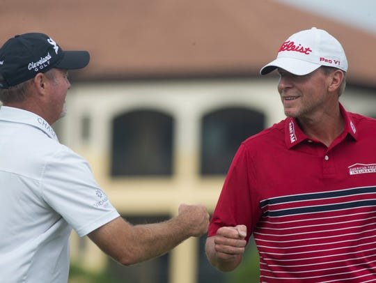Teammates Jerry Kelly, left, and Steve Stricker fist