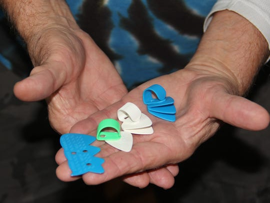 Warren Goad holds String Raker guitar picks invented by his son Brad. They still have boxes of the picks and will auction them off at Brad's celebration of life and benefit concert on Dec. 18.