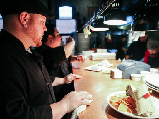 Tim Condon, executive chef, and David Morales put final touches on dishes Monday, Dec. 5, at Angry Cactus in downtown San Angelo.