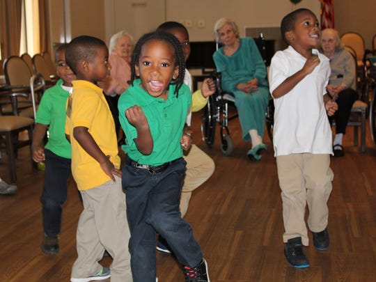 Eighty-First Street Early Childhood Center students jump around as Glen residents watch them.