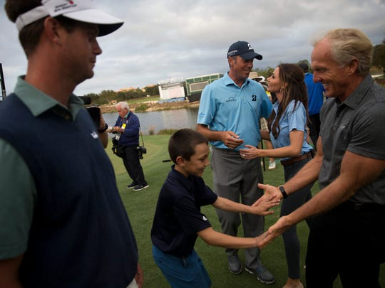 Tournament host Greg Norman receives a high-five from Cameron Kuchar, 9, after his father Matt Kuchar, in blue, claimed victory during the final round of the Franklin Templeton Shootout at Tibur—n Golf Club at The Ritz-Carlton Golf Resort Saturday, Dec. 10, 2016 in Naples.