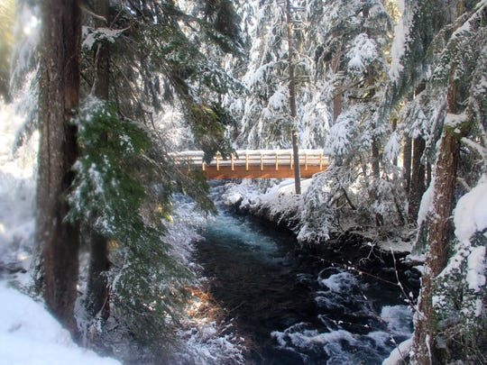 A bridge over the McKenzie River, covered in snow, connects the Waterfall Loop.