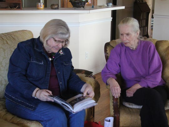 Wanda Sexton, left, shows a book to Martha Parker,