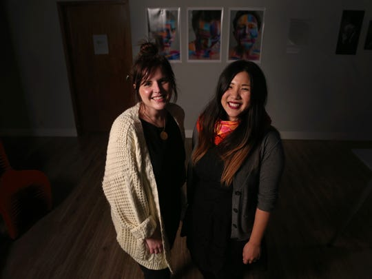 Founding members of the Girl Gang, Tia Rodemeyer and Meanz Chan, stand in front of an art display created by members of the Girl Gang on Tuesday, Nov. 29, 2016, at Gravitate in Des Moines.