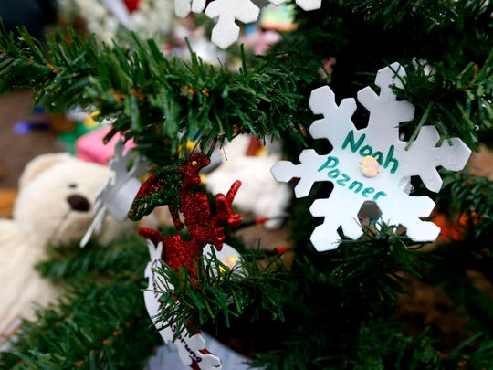 A snowflake ornament with the name of 6-year-old Noah Pozner hangs on a Christmas tree at a makeshift memorial in the Sandy Hook village of Newtown, Conn., Monday, Dec. 17, 2012, as the town mourns victims killed in Friday's school shooting. Pozner, who was killed Friday when gunman Adam Lanza opened fire inside the Sandy Hook Elementary School, will be buried Monday. (AP Photo/Julio Cortez)