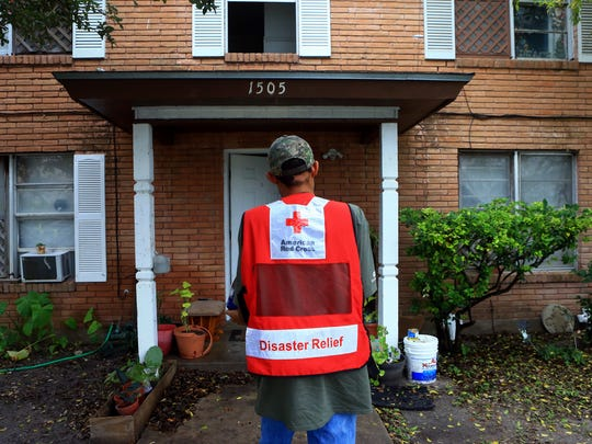 Volunteer Earnest Hysaw from the American Red Cross carries a case of water to a resident in a duplex Friday, Dec. 16, 2016, in Corpus Christi. City officials confirmed Thursday morning that one chemical contaminated the city's water supply.