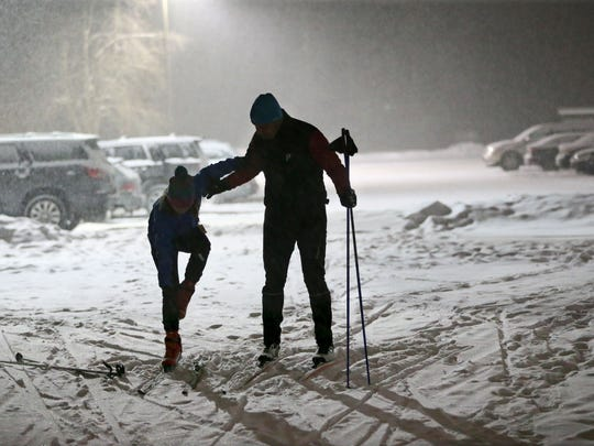 Tom Cousland of the Town of Delafield, (right) helped his daughter Sammi Cousland age 11, get her skis on as the pair prepared to head out onto the lighted cross country ski trail at the Kettle Moraine State Forest, Lapham Peak Unit near Delafield.  Snow was steadily falling as a new winter storm moved into the area.