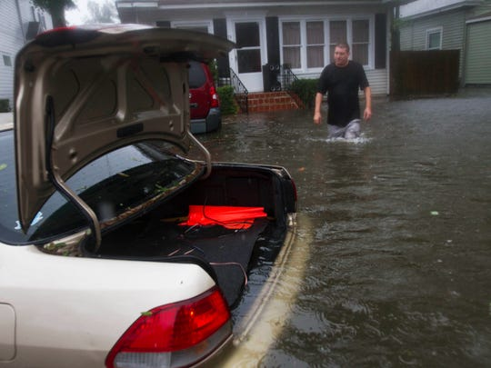 St. Augustine resident, Rob Birch checks on his flooded car Friday as Hurricane Matthew skirted the area on 10/7/2016. Downtown St. Augustine flooded during the storm.