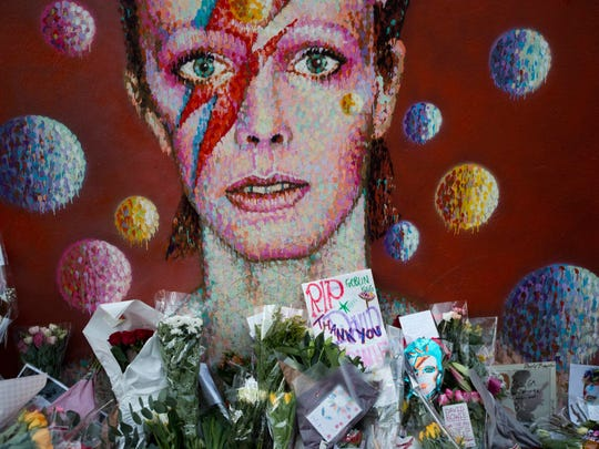 FILE - In this Tuesday, Jan. 12, 2016 file photo, tributes lie beneath a mural of singer David Bowie by artist Jimmy C in Brixton, south London. Bowie, the other-worldly musician who broke pop and rock boundaries with his creative musicianship, nonconformity, striking visuals and a genre-spanning persona he christened Ziggy Stardust, died of cancer Sunday aged 69. He was born in Brixton. (AP Photo/Matt Dunham)