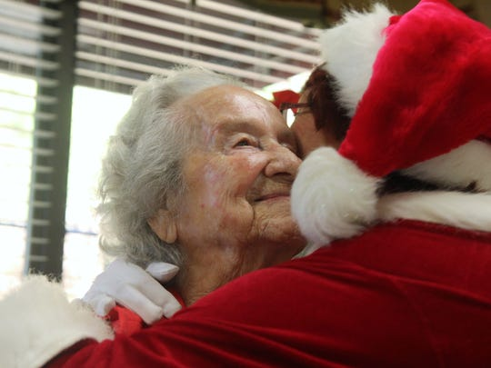 Anna Howell, left, gets a hug shortly before her 100th Christmas.