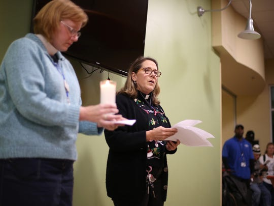 Grace Mission Pastors Amanda Nickles, right, and Jenni Liem read through a list of dozens of names of people who had passed through the doors of the Kearney Center, and died over the last year, during a National Homeless Persons' Memorial Day ceremony on Wednesday, Dec. 21, 2016.