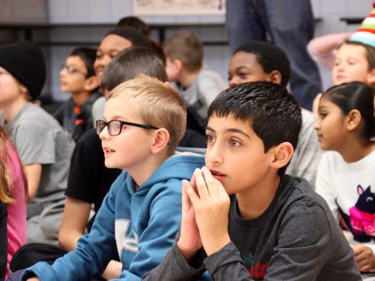 Liam Stone and Edward Toubassi (at right), fourth grade, listen to Caleb White speak about volunteerism.