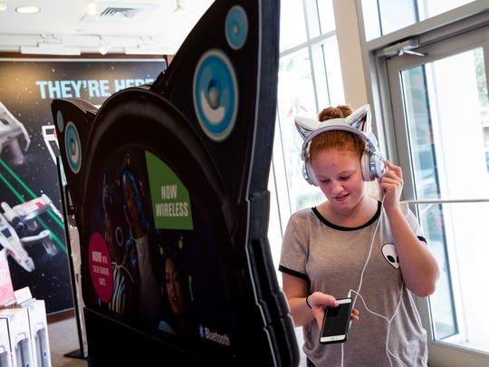 Mai Hasson, 13, tests out cat ear headphones while shopping at Brookstone at Coconut Point Mall in Estero, Fla., on Monday, Dec. 26, 2016. Holiday sales and returns surge after Christmas, bringing in crowds of shoppers.