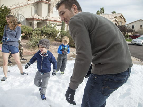 3-year-old Ryan Hesselbacher plays in snow with his
