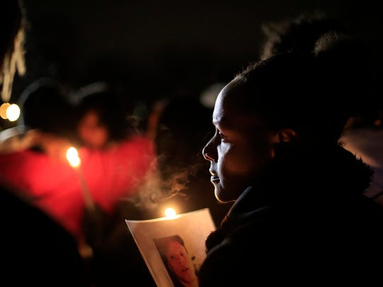 Larie Lewis holds a candle and a photo of Frederico Thompson Jr. during a vigil for Thompson at Good Park Wednesday, Jan. 4, 2017. Thompson, 18, was shot to death about 3:30 a.m. Sunday outside a southside nightclub.