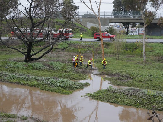Salinas firefighters check on a flooded homeless encampment off Highway 101 south of John Street on Wednesday.