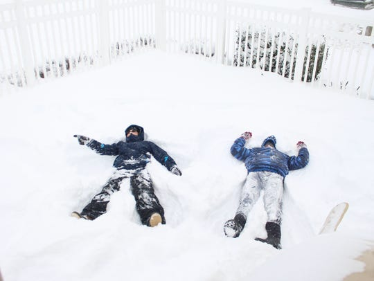 Walter Weis, 13, and Jonathan Mitchell, 12, make snow