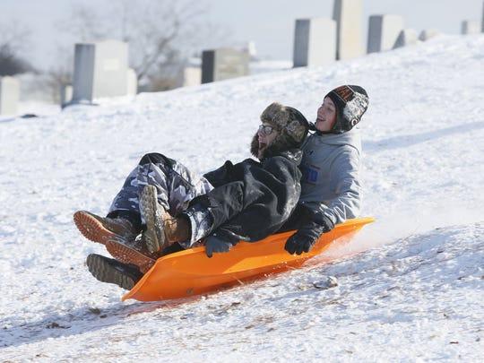 Sledders enjoy a day of sledding at Cemetery Hill near