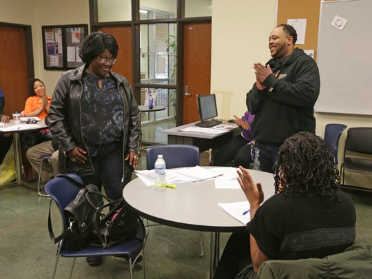 Audrea Hawkins, left, is applauded by fellow Job Club members and Career Coach Nicholas Calvert, right, after reading her elevator statement training her for future job interviews at the John Boner Neighborhood Center, 2236 East 10th St., in Indianapolis, Jan. 13, 2017.