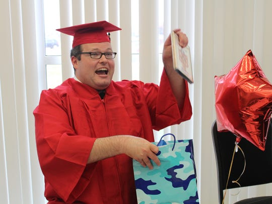 New Bossier Parish Schools graduate, Michael Duddy, smiles as he opens his family's gifts.