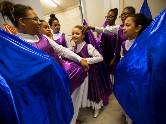 Janessa Pasco, 10, center, has her hair fixed by Didi Prudent, 12, second from left, while the Behind the Veil Flag Worship Team waits backstage during the 20th Annual Rev. Dr. Martin Luther King Jr. Parade and Celebration in downtown Naples on Monday, Jan. 16, 2017.