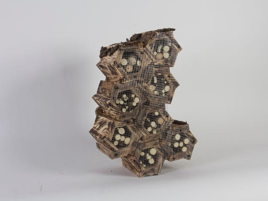 Students in the 3-D Concepts class at University of Wisconsin-Milwaukee made insect hotels from discarded wood to provide habitat for the decreasing population of bugs. This hotel, made by Erin Kruel, takes the shape of honeycombs.