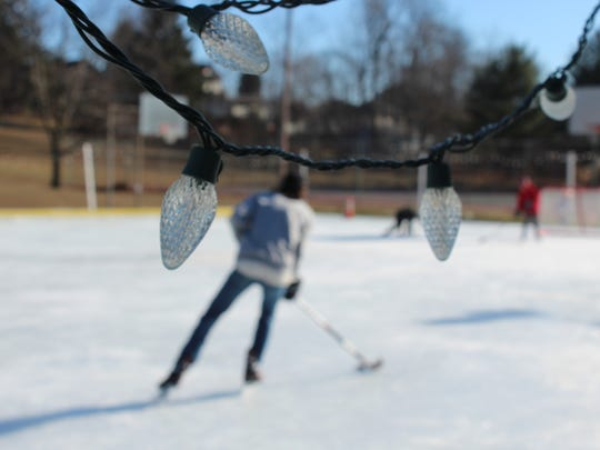 Holiday lights adorn the sides of Burlington's Calahan Park Community Rink as a skater heads down the ice on Monday, Jan. 16, 2017. The volunteer-run rink is in its fifth season of operation and draws hundreds of skaters per year.