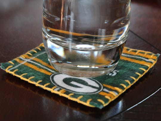 Use team fabric and gold thread to make coasters that support the Packers.