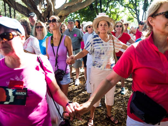 Attendees hold hands in Cambier Park in downtown Naples after the Naples Women's March for Social Justice on Saturday, Jan. 21, 2017.